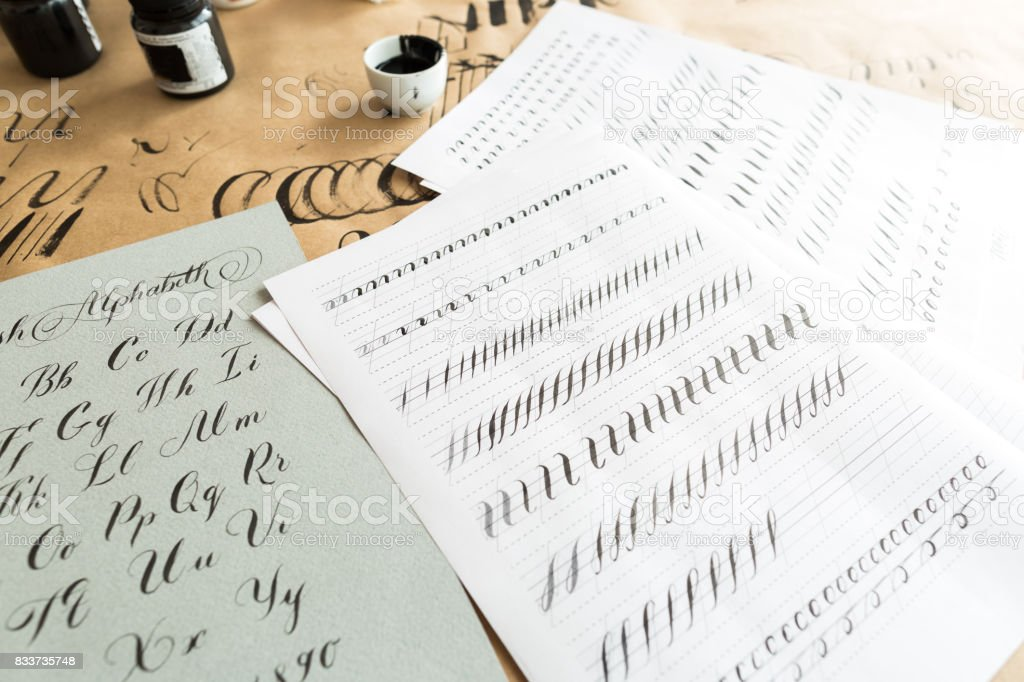 calligraphy, education, graphic design concept. lots of exercises for training skills of calligraphy with help of special supplies like black ink, brushes and white lined sheets stock photo