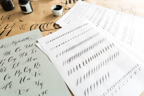 calligraphie, l'éducation, le concept de design graphique. beaucoup d'exercices pour les compétences de la formation de la calligraphie avec l'aide de fournitures spéciales comme l'encre noire, des pinceaux et des feuilles blanches lignées - graphisme photos et images de collection