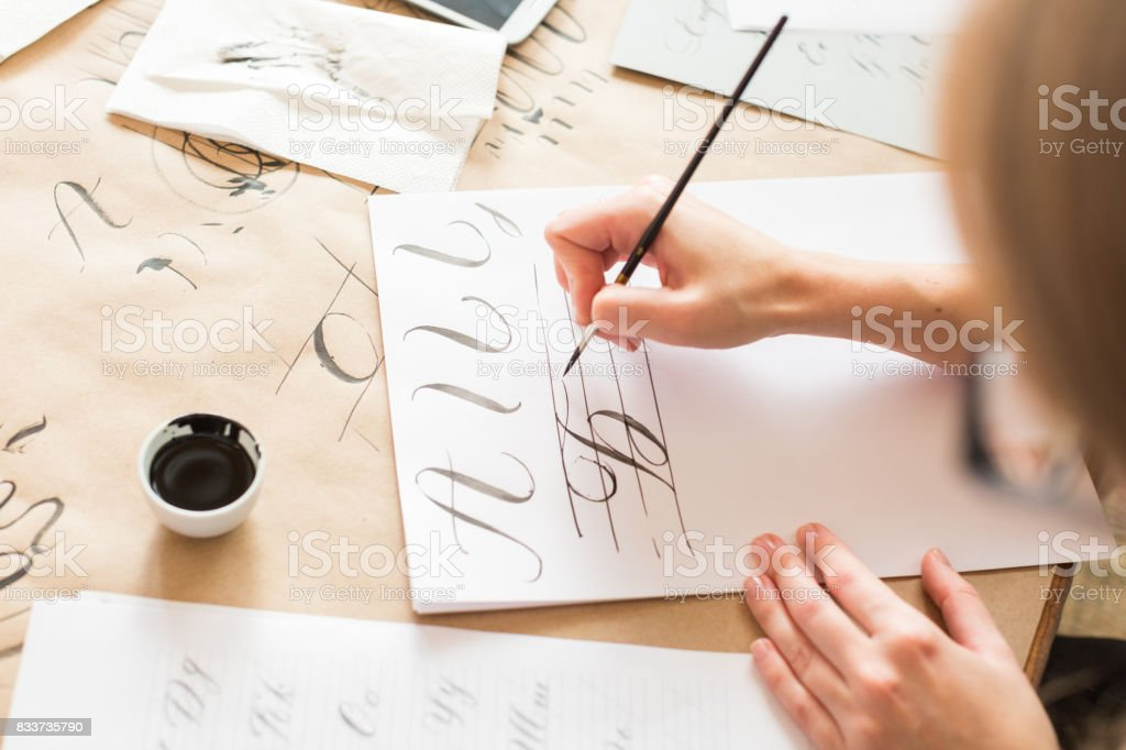 calligraphy, handwriting, technique concept. woman with beautiful elegant hands inscribing capital russian letters carefully in italic type with black ink and thin brush, drawing stock photo