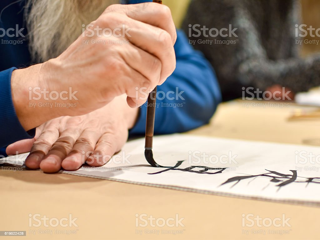 Calligraphy master drawing chinese hieroglyph stock photo