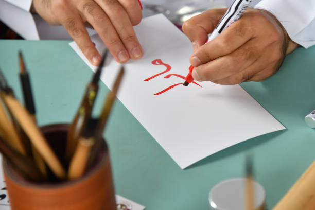 Calligraphy or decorative handwriting lettering Hands of a man writing red arabic letters on a white sheet of paper. Decorative handwriting or handwritten lettering. Calligraphy. Small depth of field. Selective focus on letter calligraphy stock pictures, royalty-free photos & images