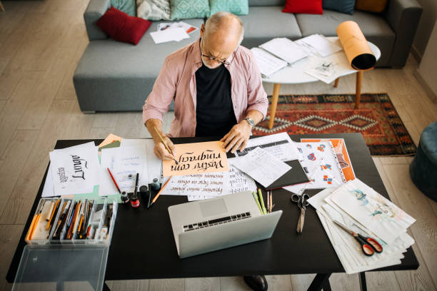 Calligraphy senior artist in his home office creating stock photo