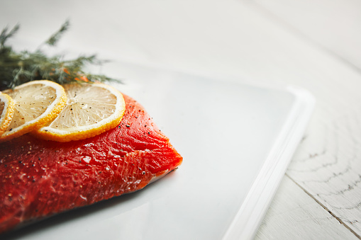 Shot of a raw piece of meat garnished with slices of lemon