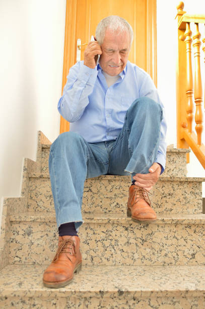 calling emergency for my accident at home - old man feet stock photos and pictures