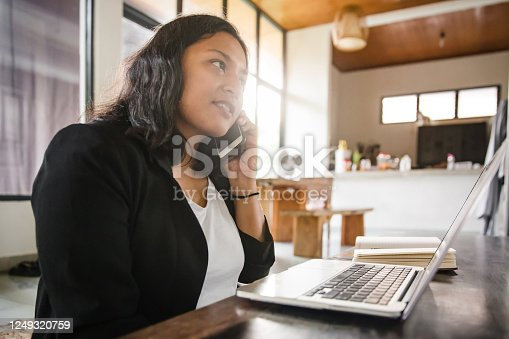 A shot of a young college graduate calling for a job interview from home