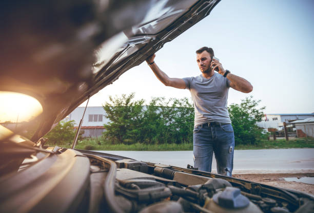 Calling roadside assistance Young man calling roadside assistance after car breakdown aground stock pictures, royalty-free photos & images