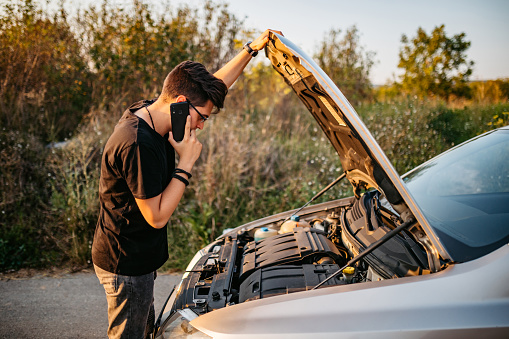 Young handsome Caucasian man had a car breakdown and calling roadside assistance.