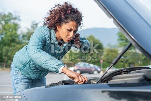 860373412 istock photo Calling roadside service after car engine breakdown 1054663300