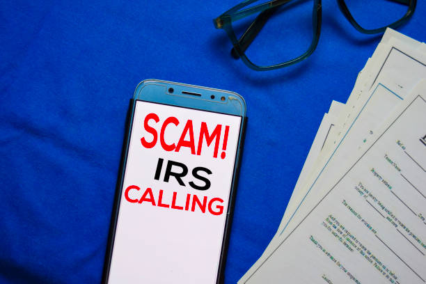 SCAM! IRS Calling text on Smart Phone isolated on office desk. stock photo