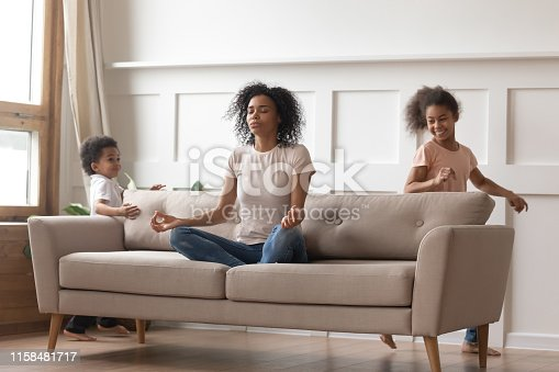 istock Calm african mom doing yoga on sofa relaxing with kids 1158481717