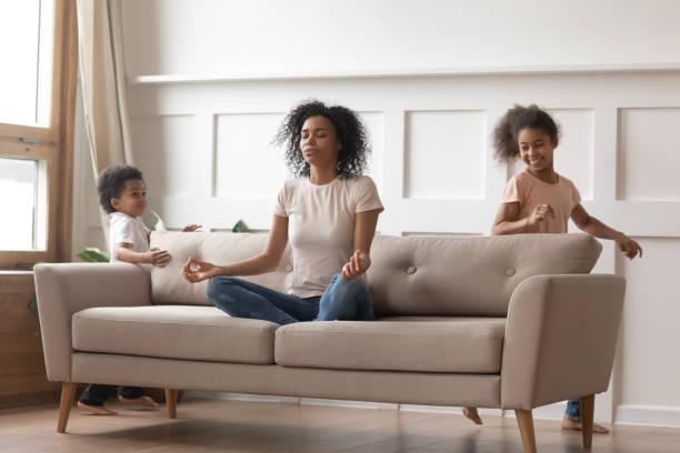 mamã africana calma que faz a ioga no sofá que relaxa com miúdos - consciencia negra - fotografias e filmes do acervo