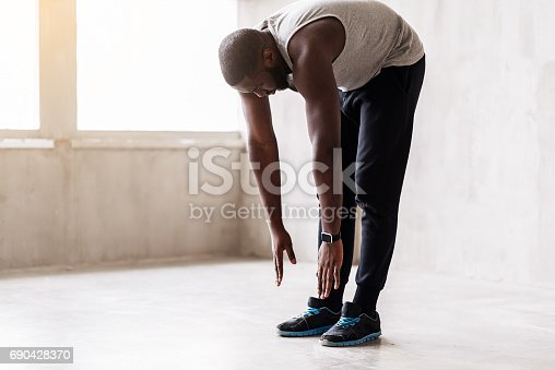 Concentrated bearded sportsman is standing on straight legs and making forward bend. Focus on smart watch and sport shoes