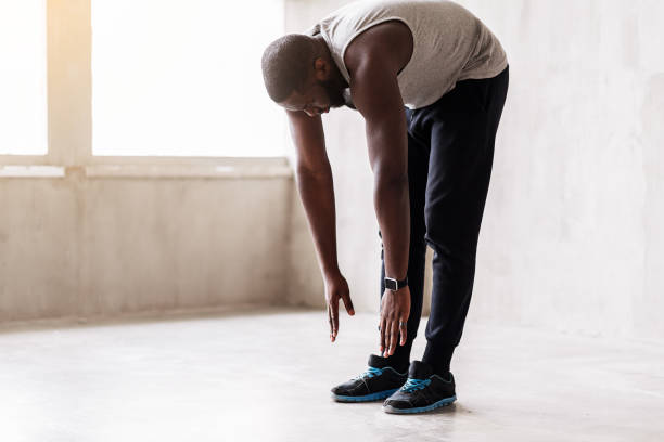 Calm african muscular guy doing warming-up exercises Concentrated bearded sportsman is standing on straight legs and making forward bend. Focus on smart watch and sport shoes bending stock pictures, royalty-free photos & images