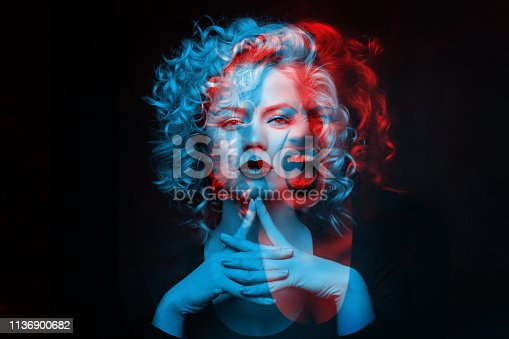 istock Calm and angry girl. Double color exposure. 1136900682
