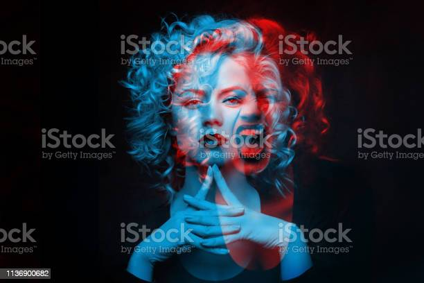 Photo of Calm and angry girl. Double color exposure.