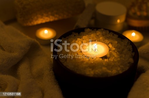 Salt bath concept.Dark and quiet atmosphere.Closeup of sea salt in the bowl and candles