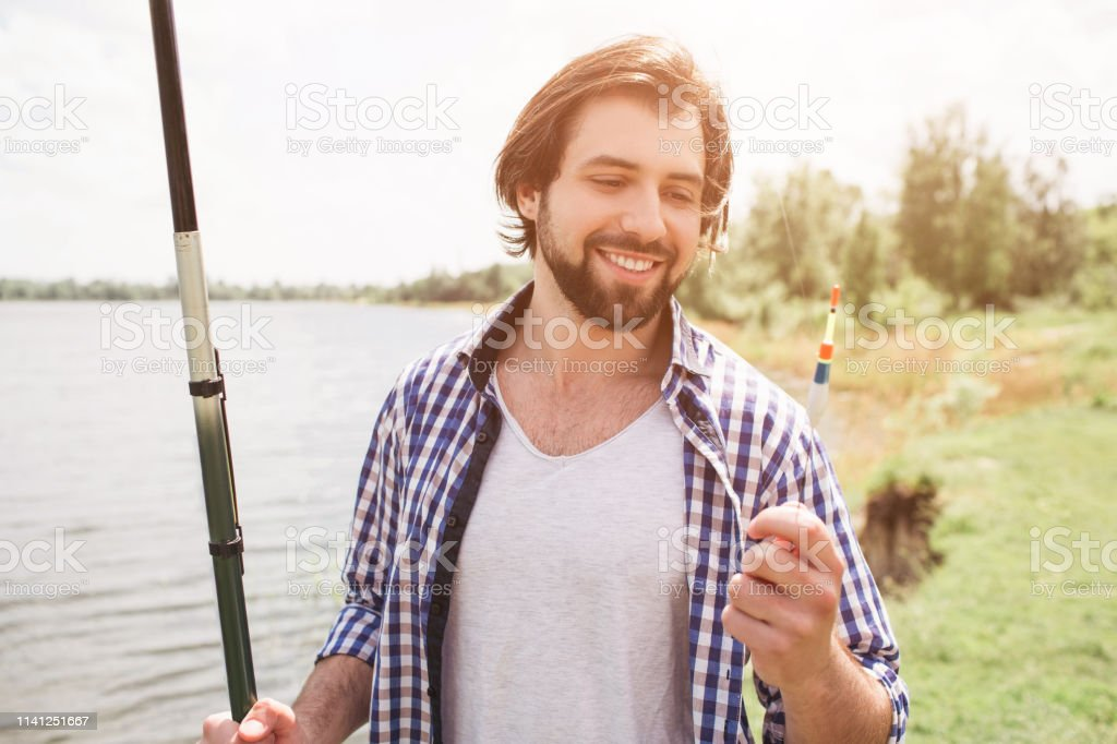 Calm and thoughtful guy is standing at the edge of lake and looking...