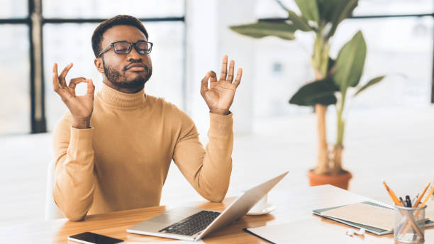 Calm black guy meditating while doing homework Stress Management. African student meditating, working on laptop, missing deadline. Panorama, free space well structure stock pictures, royalty-free photos & images
