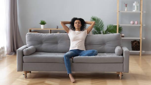 mulher preta calma que relaxa no sofá confortável na sala de visitas - consciencia negra - fotografias e filmes do acervo