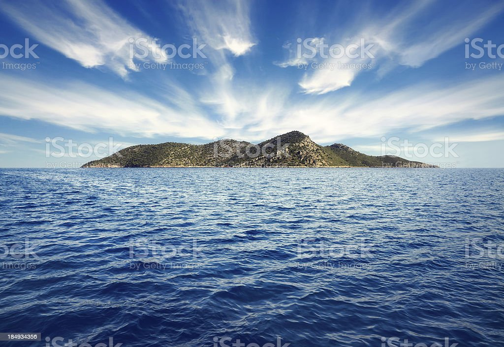 Calm blue water surrounds an island royalty-free stock photo