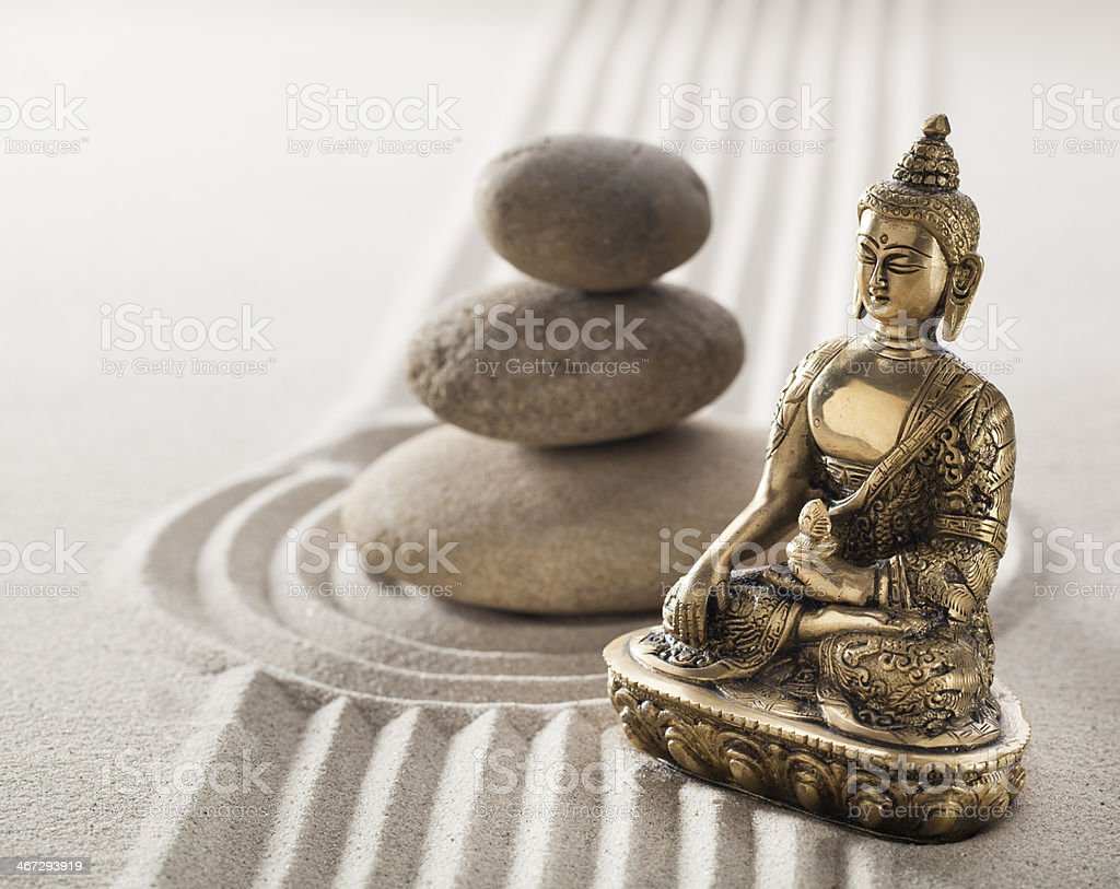 calm Buddha and balancing stones in sand lines and curves royalty-free stock photo