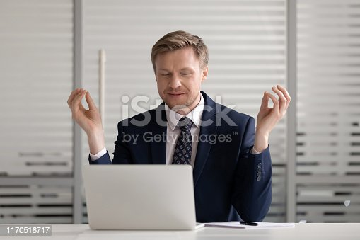 916520034istockphoto Calm businessman distracted from work mediating at workplace 1170516717