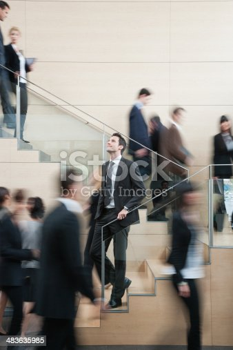 483635979 istock photo Calm businessman in busy office staircase 483635985