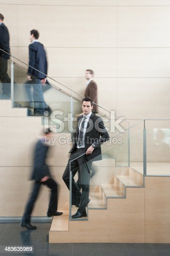 483635979 istock photo Calm businessman in busy office staircase 483635989
