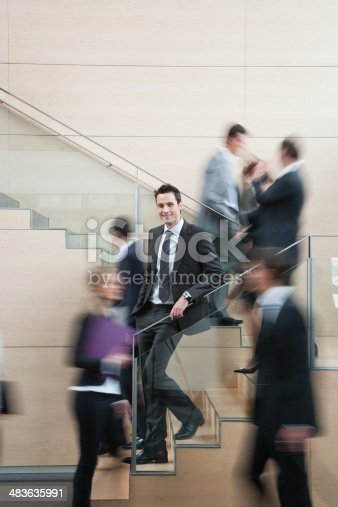483635979 istock photo Calm businessman in busy office staircase 483635991