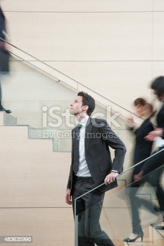483635979 istock photo Calm businessman in busy office staircase 483635995