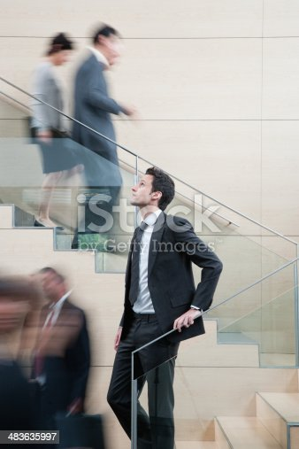 483635979 istock photo Calm businessman in busy office staircase 483635997