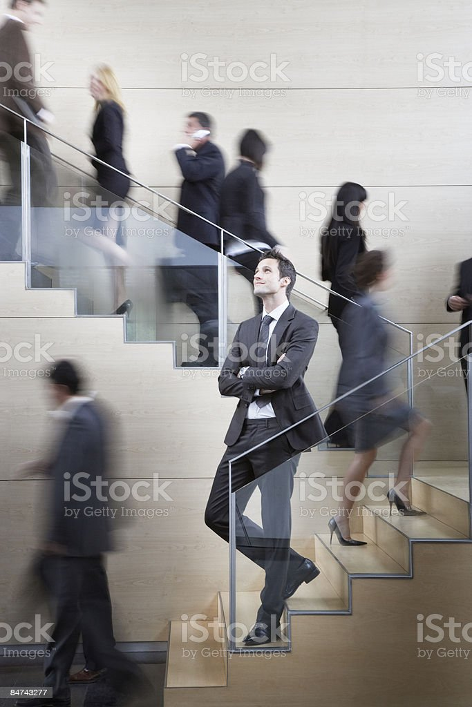 Calm businessman in busy office staircase royalty-free stock photo