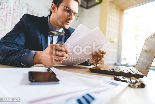 Composed stubbled male reading documents while sitting at table in cozy apartment