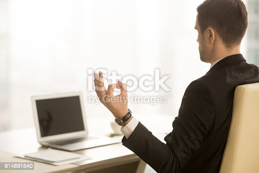 916520034istockphoto Calm businessman meditating in workplace, chin mudra, yoga at work 914891540