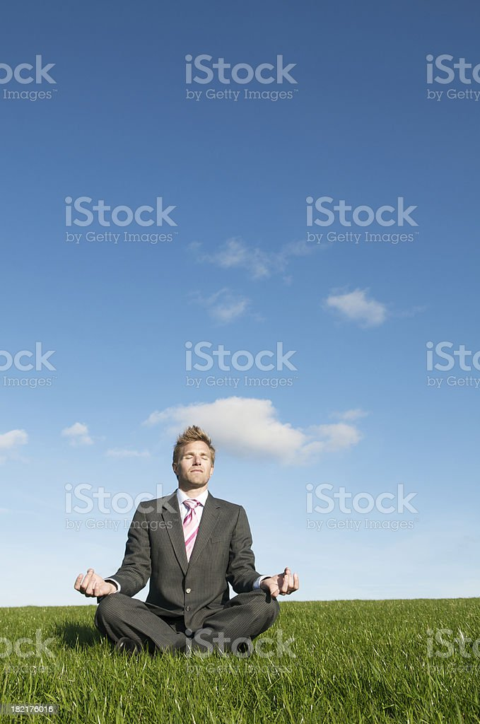 Calm Businessman Meditating Outdoors in Empty Meadow royalty-free stock photo