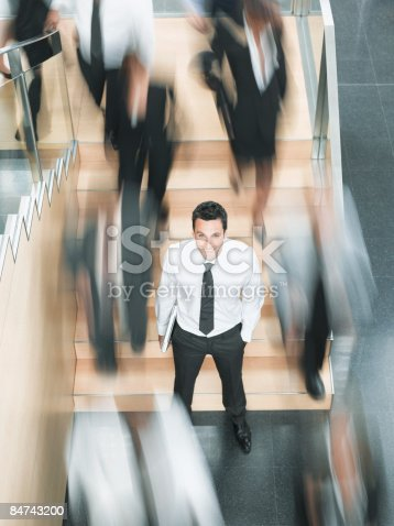 483635979 istock photo Calm businessman standing in busy office 84743200