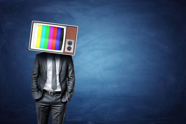 A calm businessman with hands in his pockets wears an old TV box with color bars on the screen stock photo