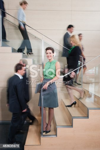483635979 istock photo Calm businesswoman in busy office staircase 483635975