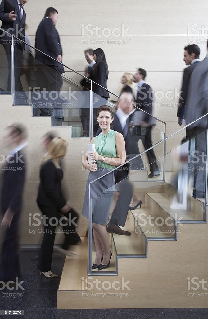 Calm businesswoman in busy office staircase royalty-free stock photo