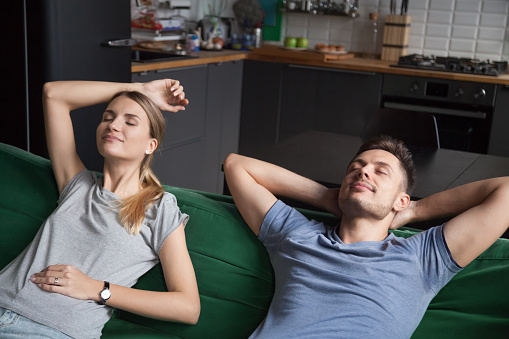 973962076 istock photo Calm carefree couple enjoying peaceful rest relaxing together on couch 1028900542