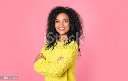 857924506 istock photo Calm confidence. Determined Afro-American girl in a light yellow sweater is posing in half profile with folded arms, her head turned towards the camera, smiling broadly. 1182101030