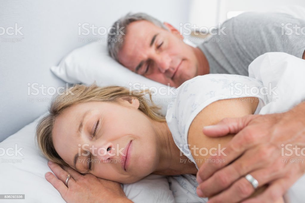 Calm couple sleeping and spooning in bed stock photo