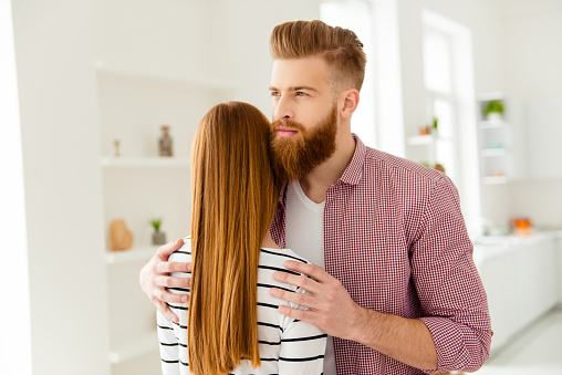 istock Calm down quarrel stress depression concept. Portrait of happy cunning curious guy thinking about something else and hugging her girlfriend wearing red checkered casual shirt striped sweater 982384726