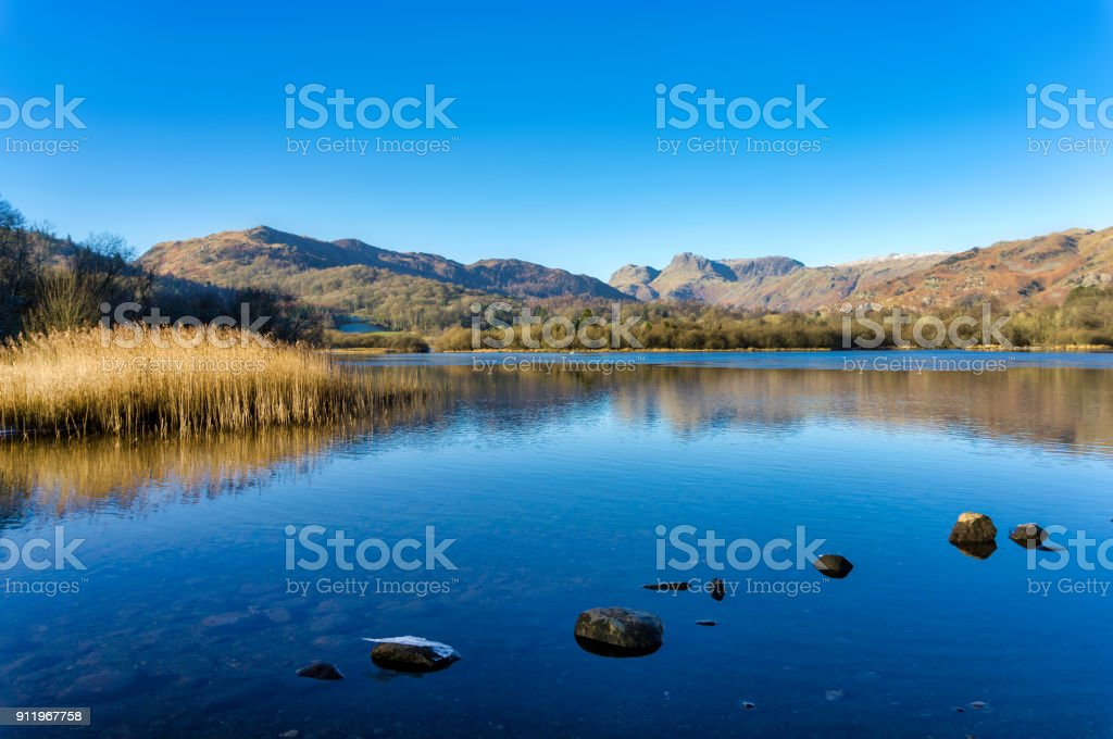 A calm Elterwater with the Langdale Pikes in the distance stock photo