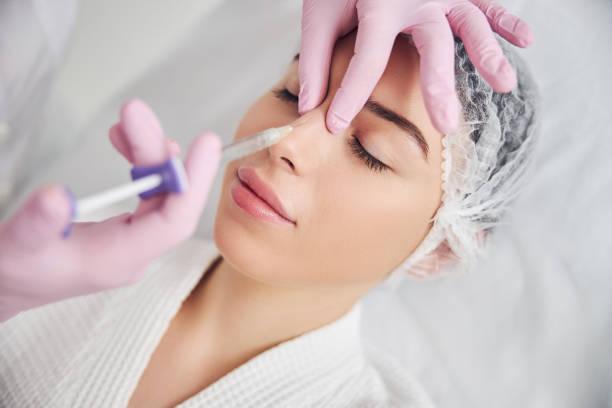 Calm female patient undergoing injectable beauty procedure stock photo
