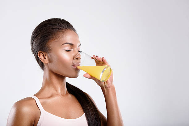 calm fit woman is drinking juice - drinking juice stock photos and pictures