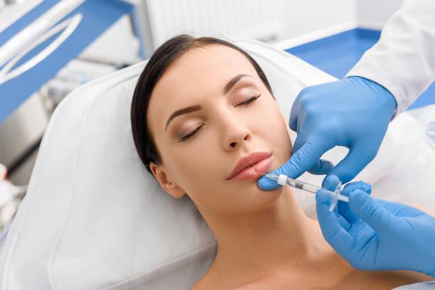 Calm girl getting cosmetic procedure stock photo