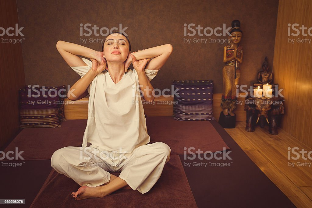 Calm girl stretching her body with masseur stock photo
