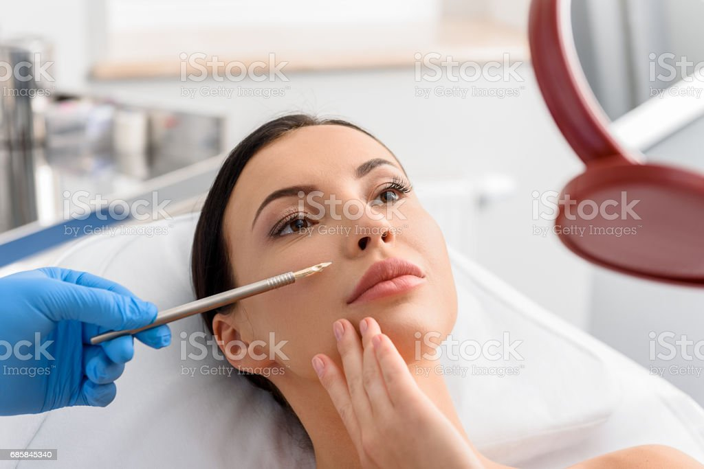 Physician demonstrating problem-prone skin of serene lady in hospital...