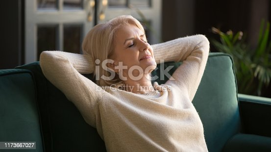 973962328 istock photo Calm happy old woman relaxing with eyes closed on couch 1173667027